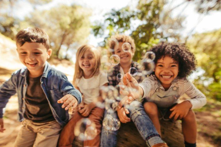niños jugando a pompas juntos