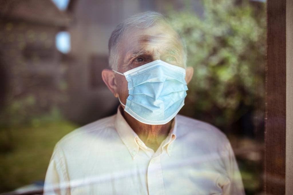 anciano a traves de ventana con mascarilla