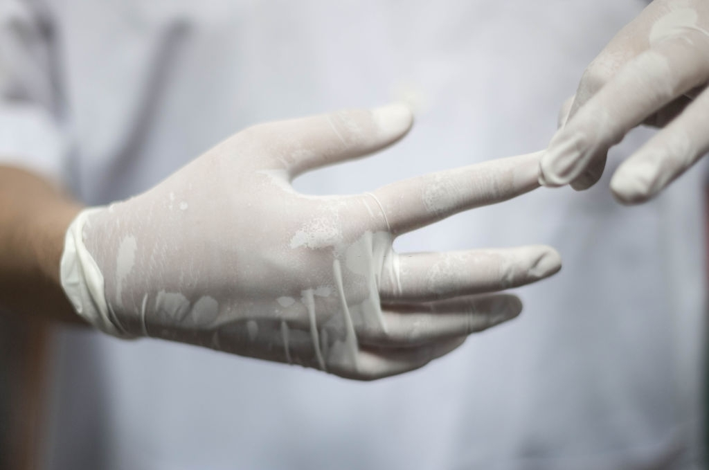 mujer quitandose guantes blancos desechables