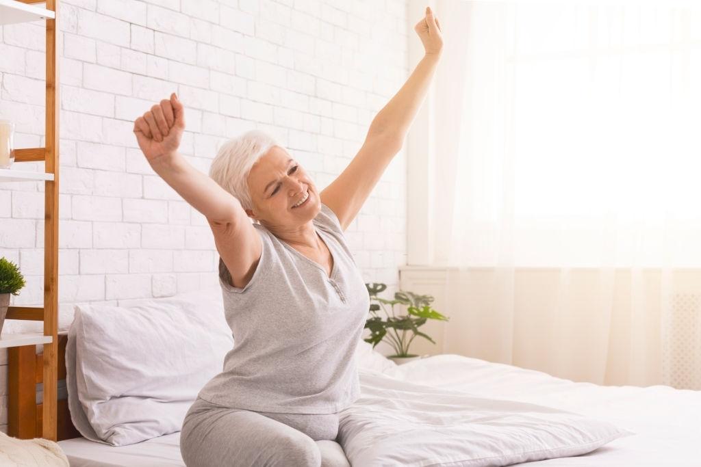 mujer mayor tras buena noche de sueño en cama articulada