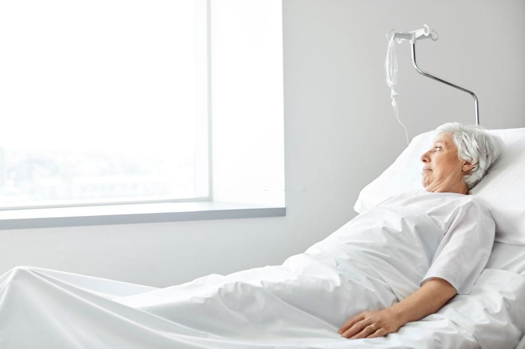 anciana mirando a ventana de hospital desde la cama