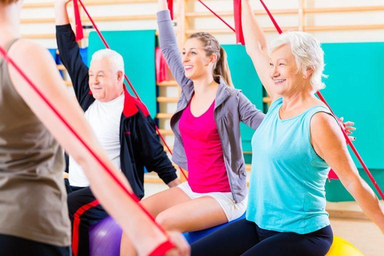 ancianos con bandas elasticas haciendo ejercicio