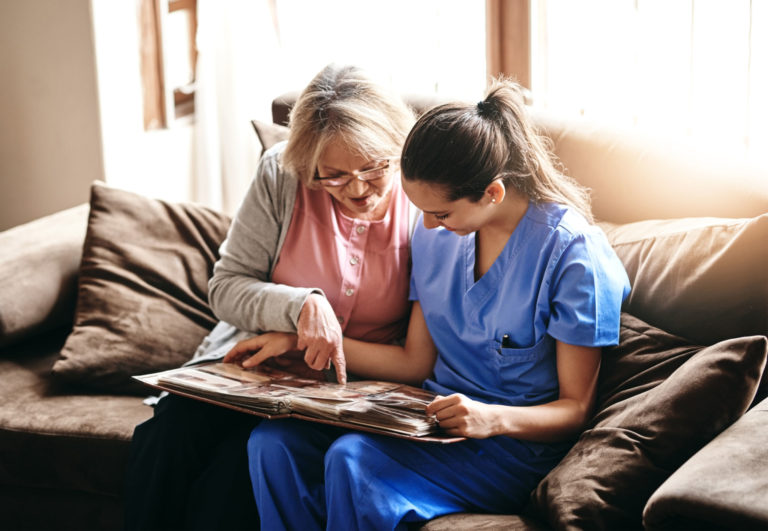 enfermera con persona mayor mirando fotos