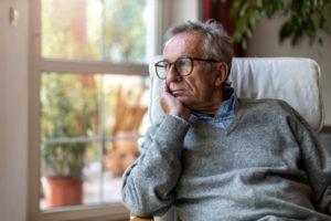 hombre mayor mirando por la ventana
