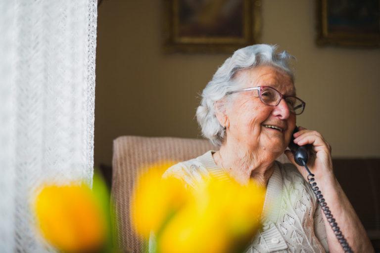 mujer mayor con telefono fijo