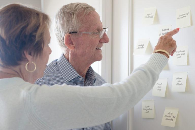 personas mayores senalando notas en frigorifico
