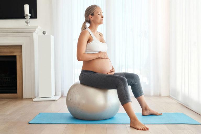mujer embarazada sobre bola de ejercicios