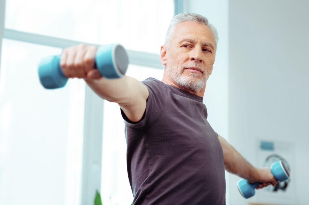 anciano levantando peso en casa